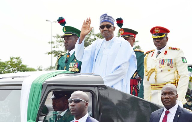 President Buhari acknowledges cheers from viewers while inspecting Guard of Honour at Independence Day parade